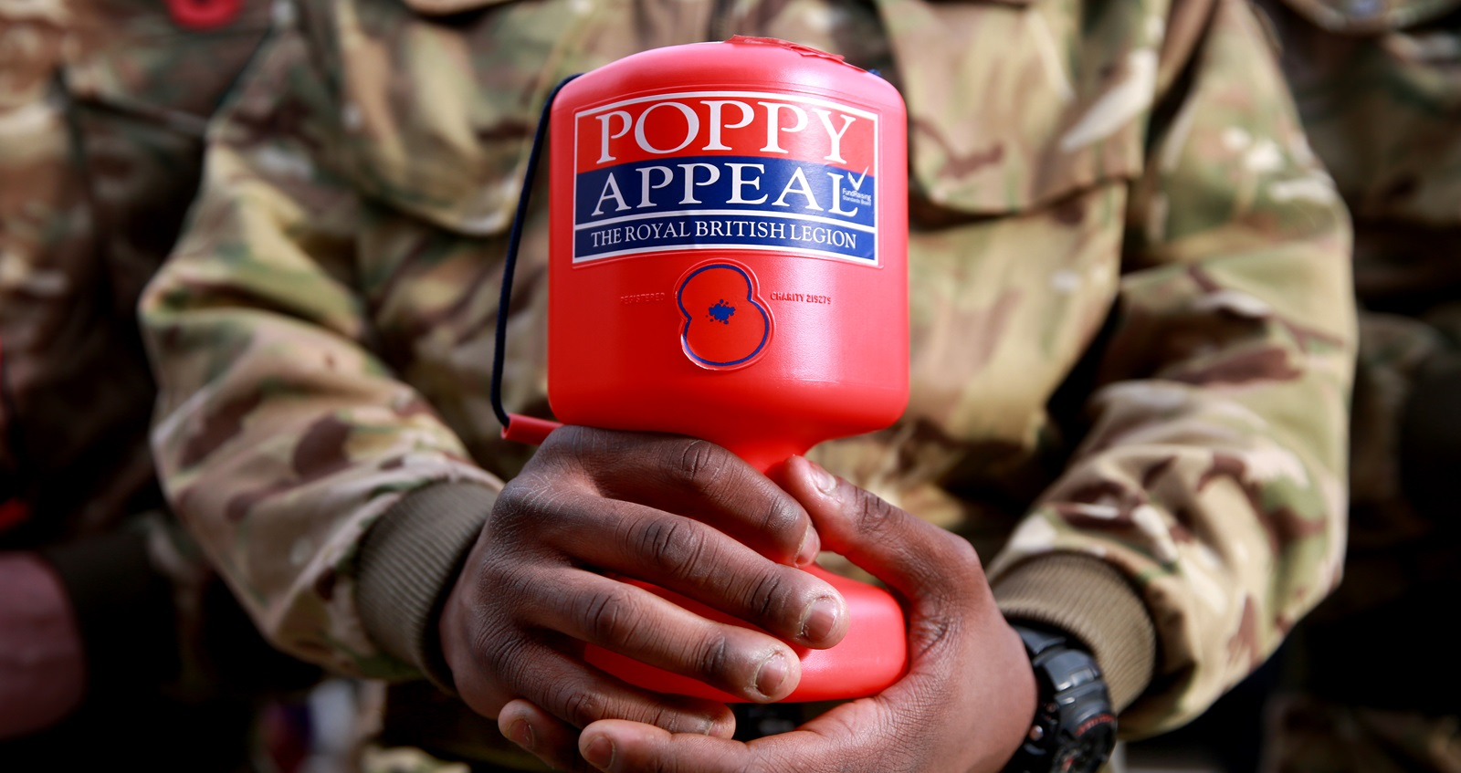Royal British Legion Poppy Appeal collector in battledress holding red collection box