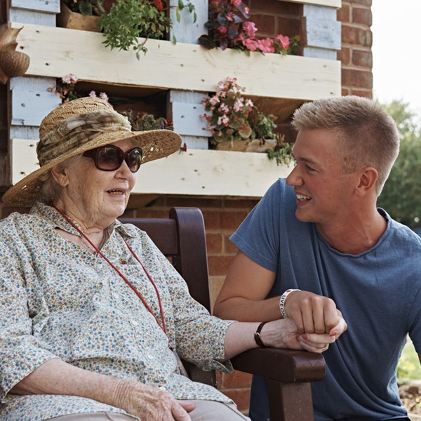 A resident holding hands with a care assistant at a Royal British Legion care home