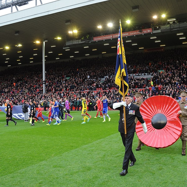 A poppy is carried onto the pitch at Anfield, Liverpool FC stadium