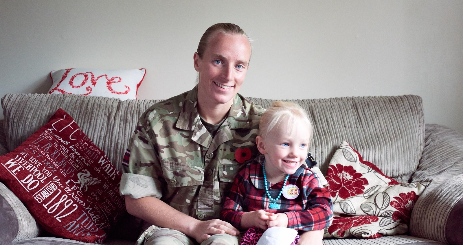 Army Healthcare Assistant in battledress at home with young daughter