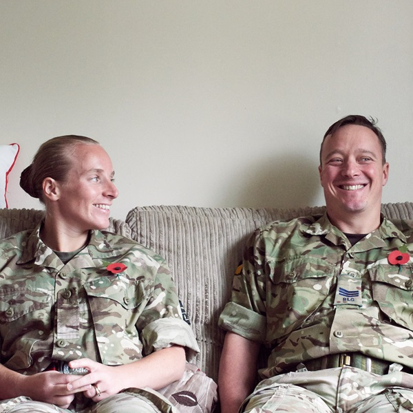 Military couple, and members of the Legion, sitting on sofa at home in battledress