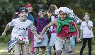 Two boys holding hands and running at a Royal British Legion Youth Membership event