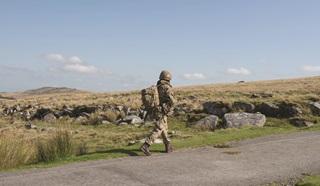 Soldier walking alone along roadside
