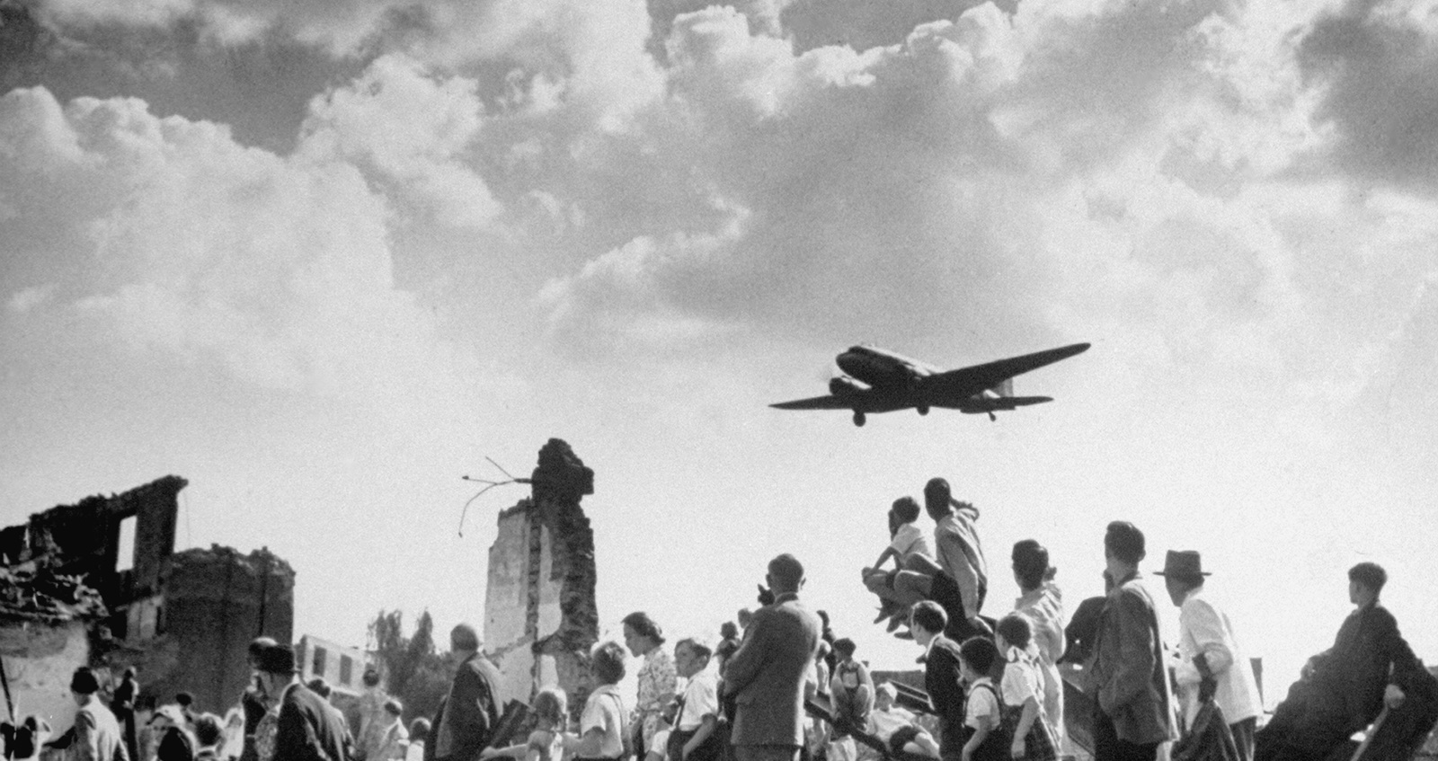 People standing on rubble as plane flies overhead during the Berlin Blockade
