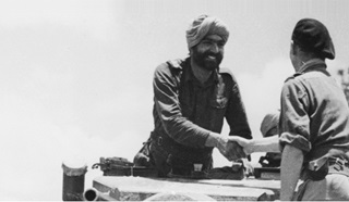 Meeting at MS 109 of the 7th Cavalry and 33 Corps. Jemader Karnail Singh of 7th Cavalry shakes hands with Major AC T Brotherton, a 33 Corps Staff Officer (Credit: @IWM HU 88980)