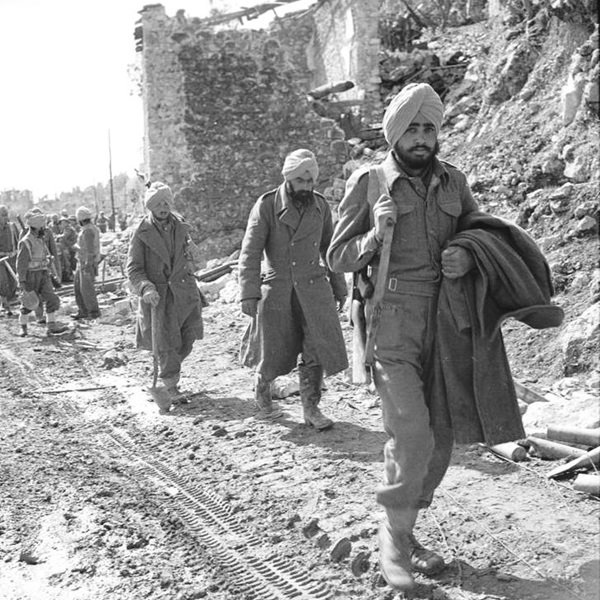 Second Battle of Monte Cassino, 1944: Indian troops pass bomb shattered buildings on the outskirts of Cassino town.