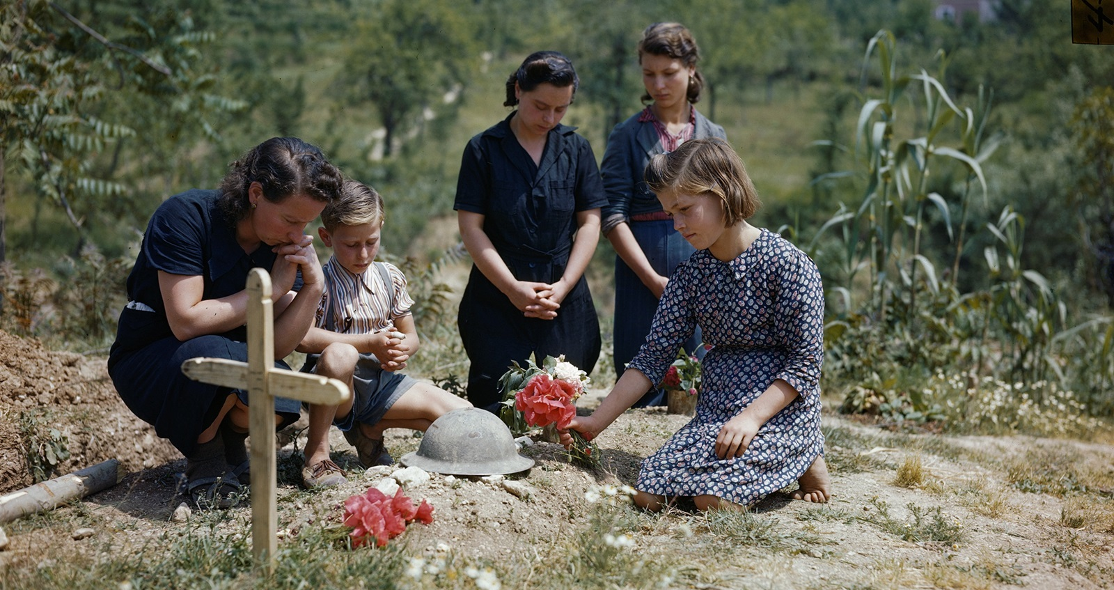 A family places flowers on the grave of an unknown British soldier killed at Cassino.  Credit: ©IWM (TR 001802)