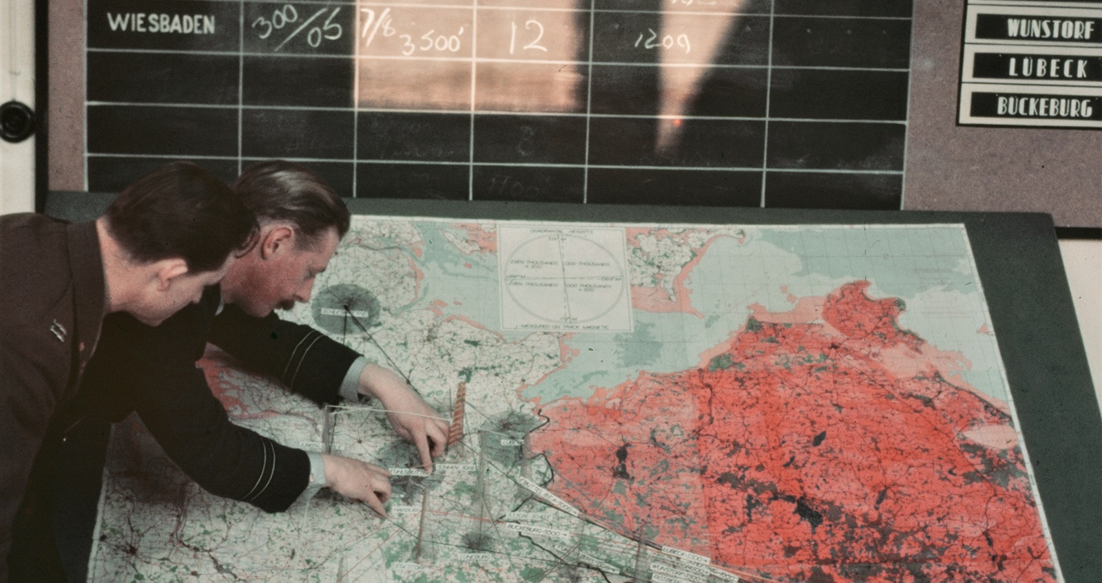 British and American air force officers consult an operations plan giving routes and heights of all aircraft in and out of the Berlin area during the Airlift.