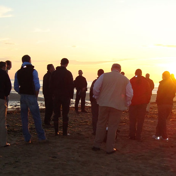 People gathered at sunset on a Normandy beach remembering D-Day.