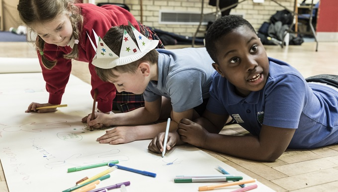 Children at a Military Kids Club Heroes drawing together on the floor.