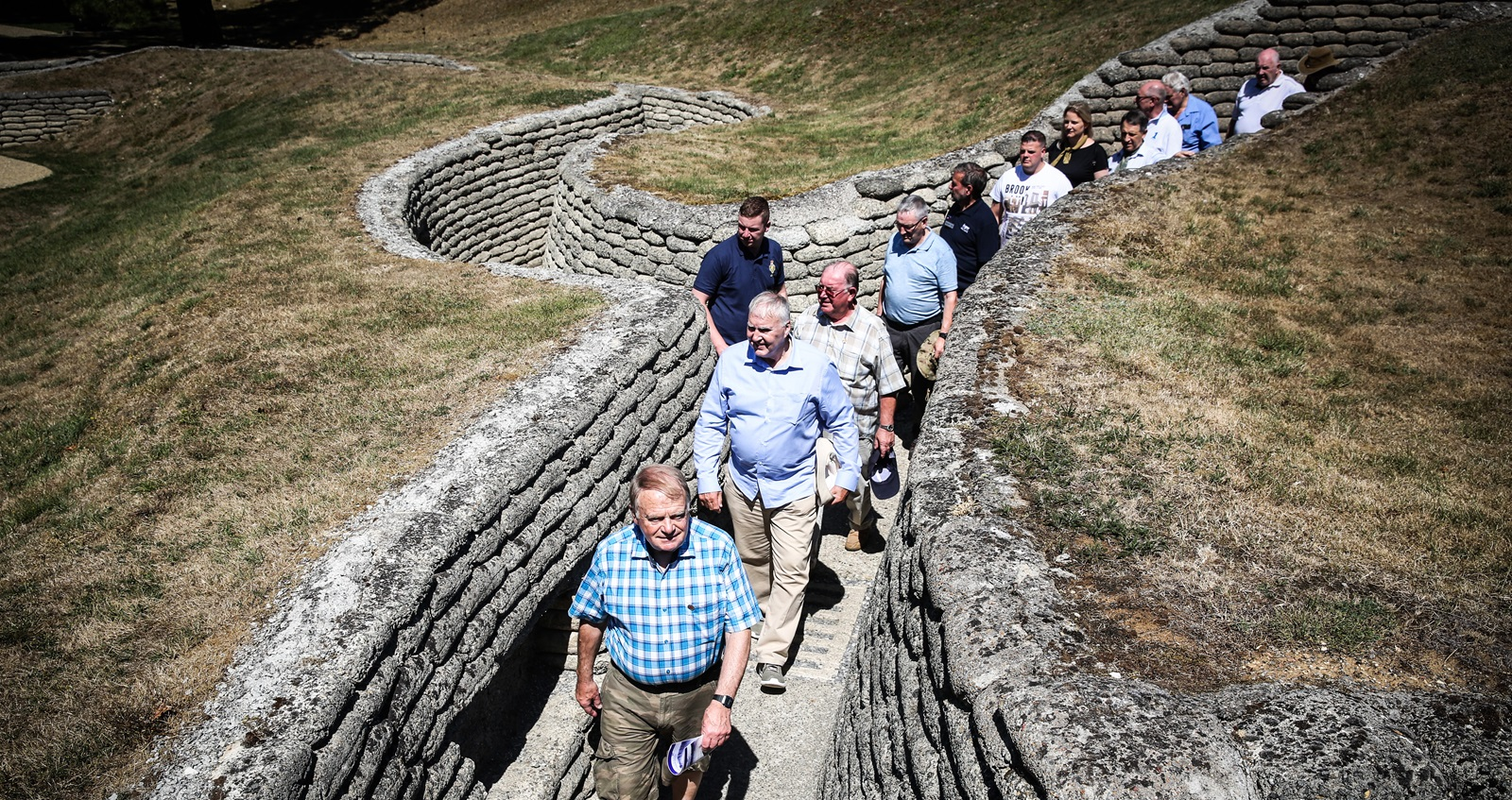 Men walking in stone wall trenches on a Remembrance Travel Great Pilgrimage