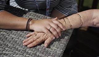 An Admiral Nurse holding the hand of an elderly female veteran