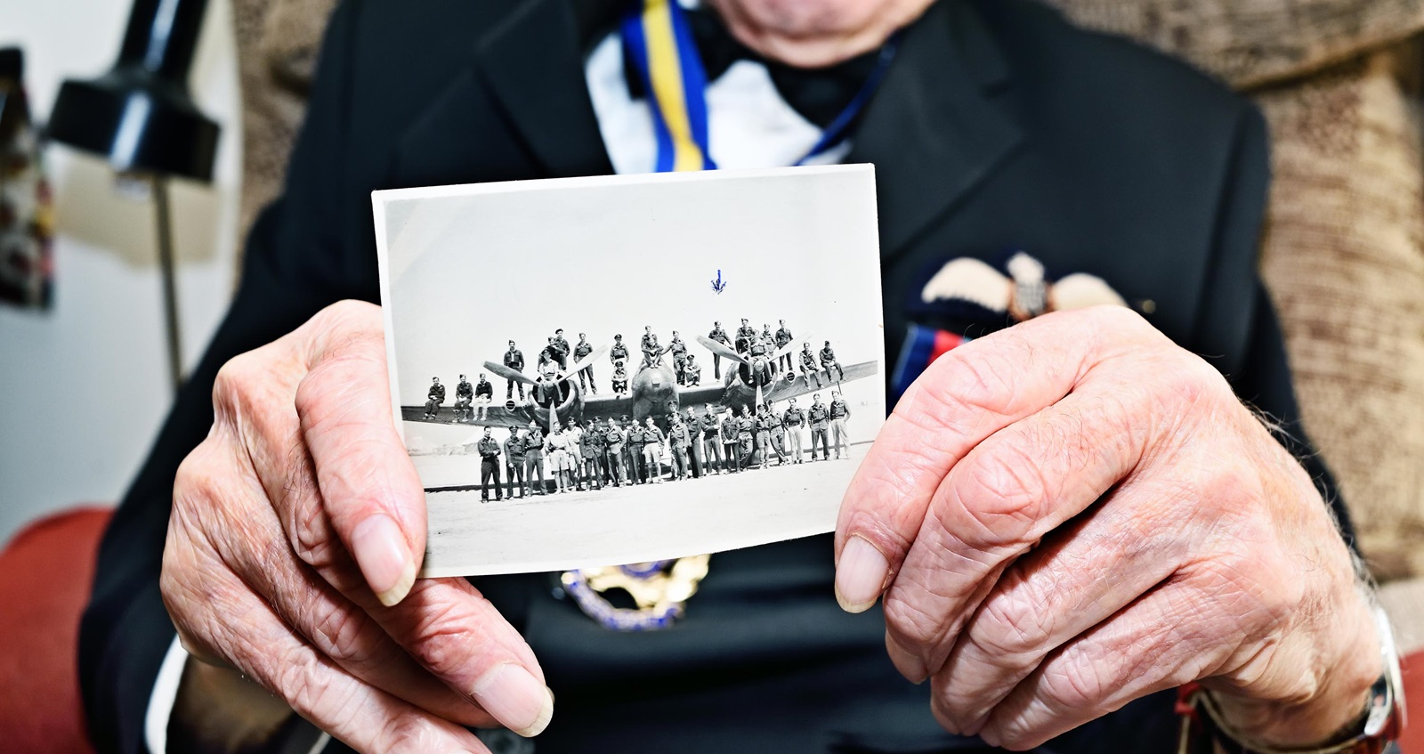 Bill Harrison holds photo of 603 Squadron crew from 1944