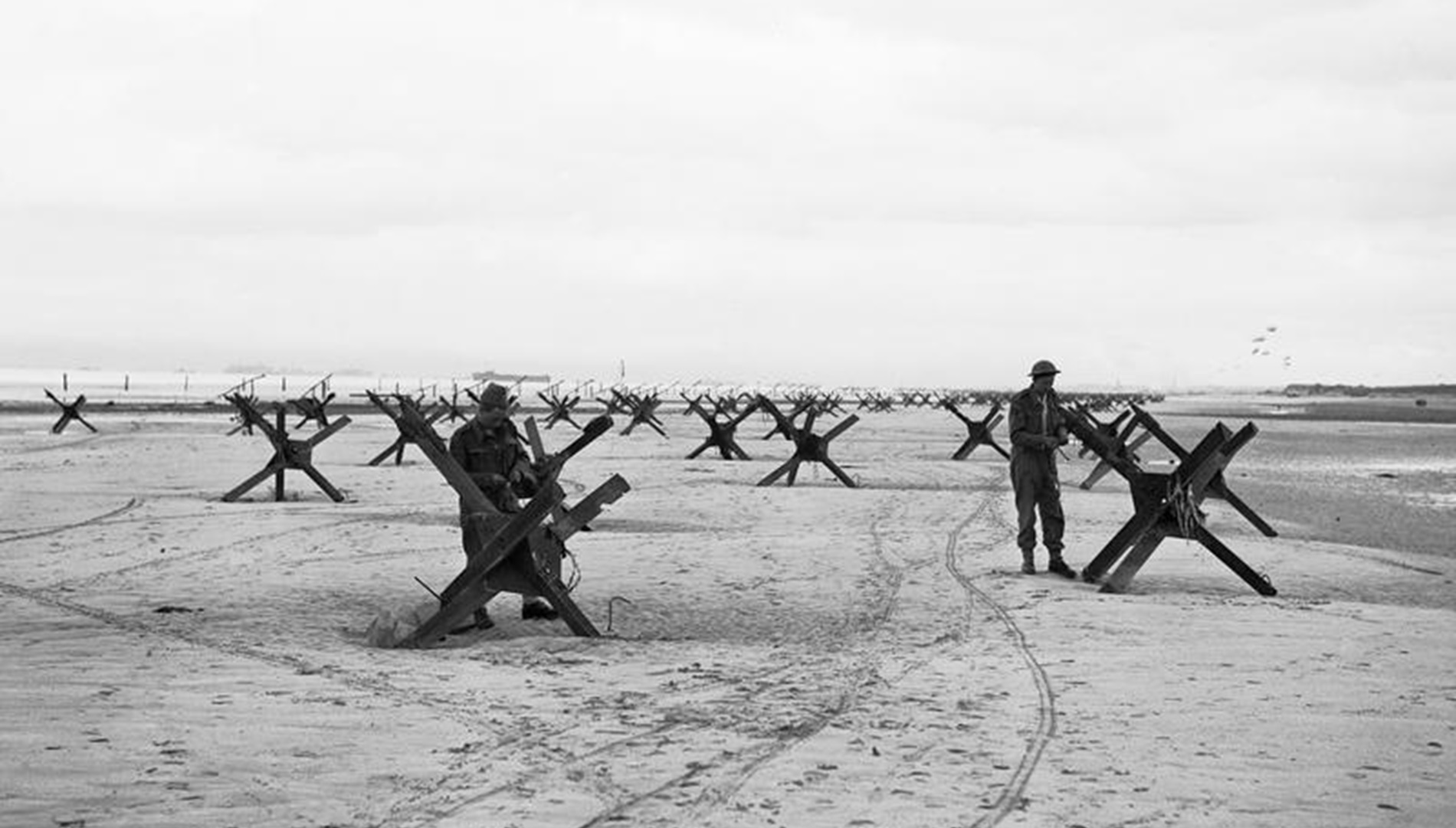 Royal Navy Commandos preparing to demolish beach obstacles designed to hinder the advance of an invading army.