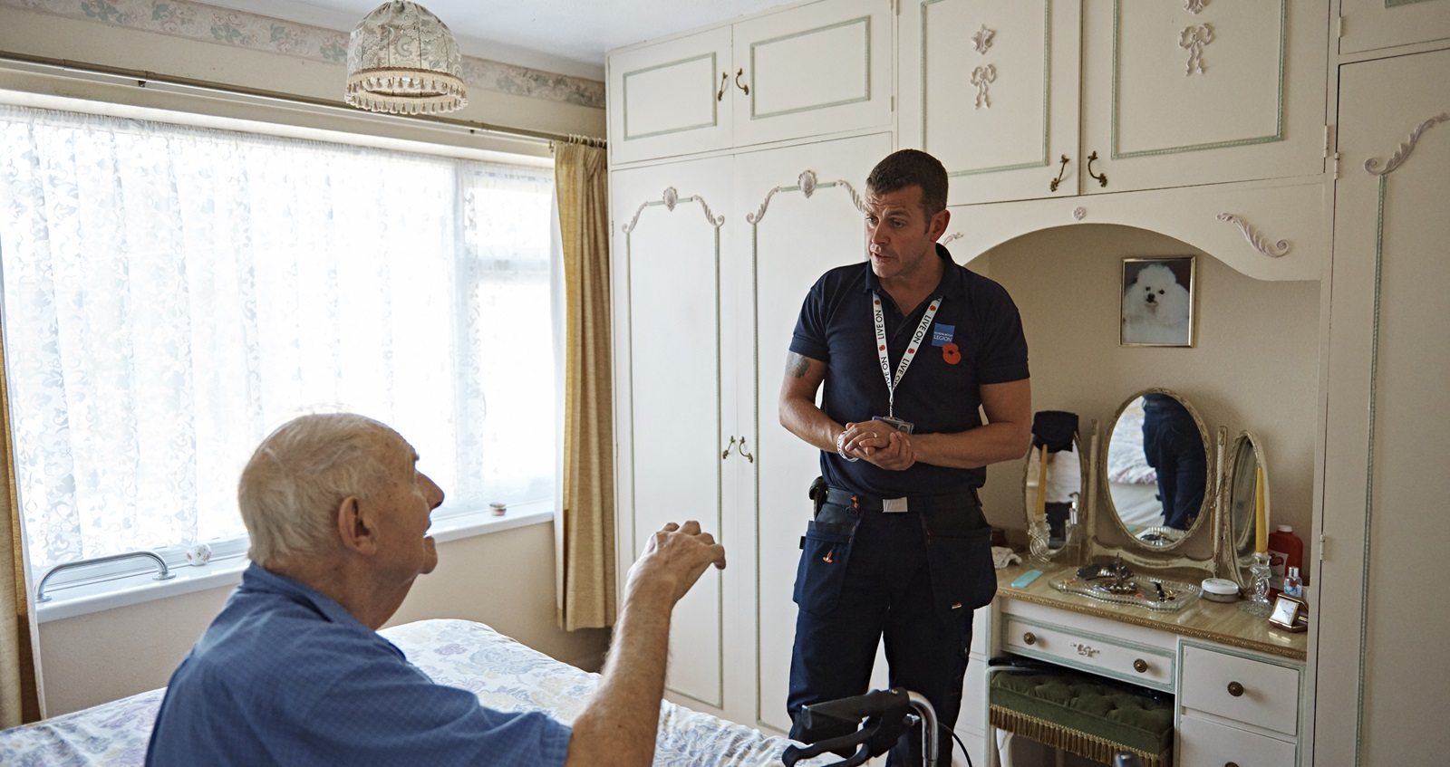 A member of Royal British Legion staff speaking to a veteran
