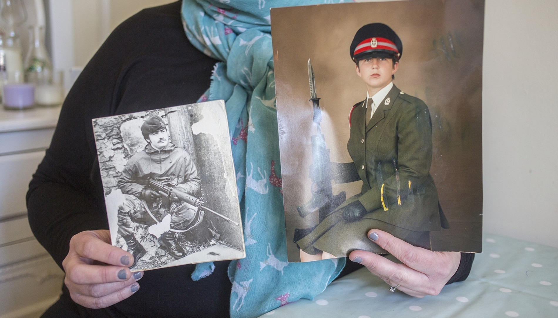 Stacey holding photos of her time in the Army