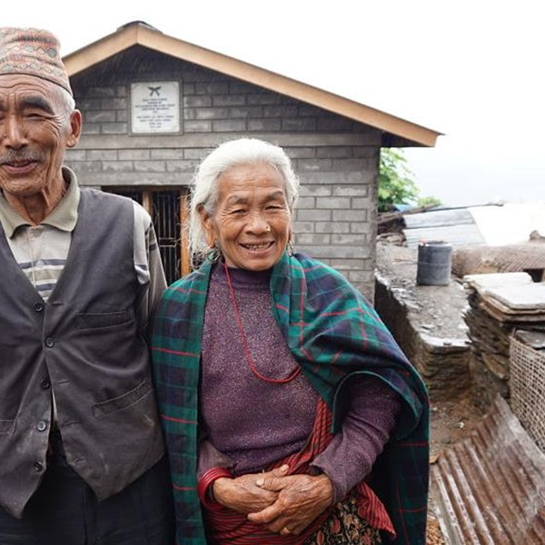 Baldhan and Budhini stood outside their newly build earthquake resistant home