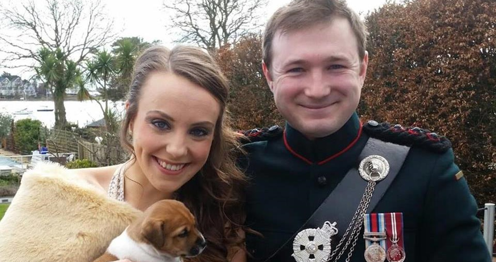 Victoria holding a puppy and standing with her husband.