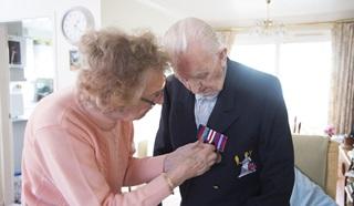 Betty pinning Reggie's medals on his blazer