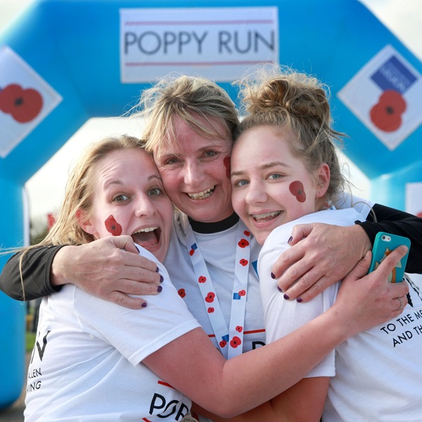 Three Poppy Run London participants hugging at the end of the race.